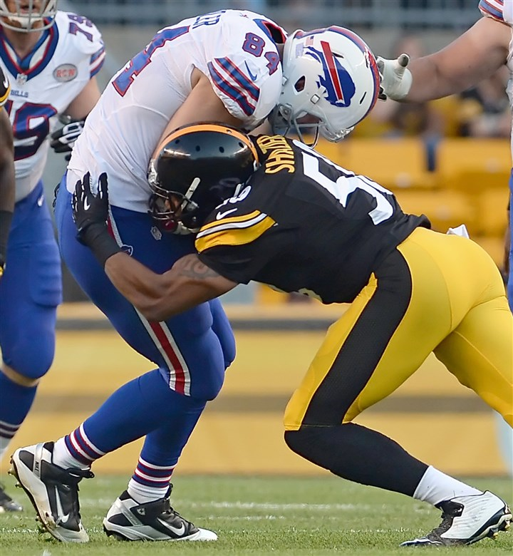 20140816mfsteelerssports11-2 Rookie linebacker Ryan Shazier takes down the Bills' Scott Chandler in the first quarter at Heinz Field Saturday night.