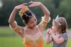 "Chloe Olson, 13, helps Ellie Rizk, 4, of Morningside, strike a ballet pose before the start of the Pittsburgh Ballet Theatre's ""Ballet Under the Stars."""