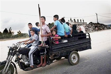 gazaM-2 Palestinians flee their destroyed neighborhood to head to a United Nations school to take refuge for the night Monday in the northern Gaza Strip city of Beit Hanun. Prime Minister Benjamin Netanyahu warned that Israel will hit back hard if Palestinian rocket attacks from Gaza resume, speaking just hours before the midnight expiry of a five-day ceasefire.