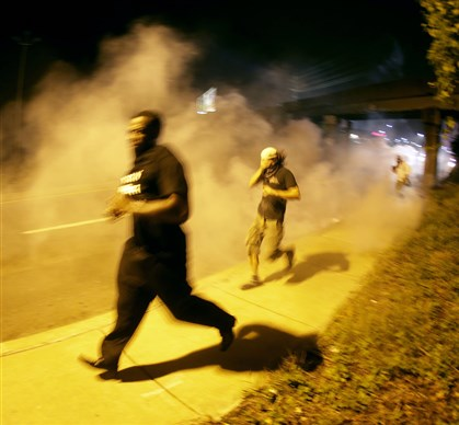 "Police Shooting Missouri People run from tear gas after police dispersed a crowd Sunday during a protest for Michael Brown, 18, who was killed by a police officer Aug. 9. Missouri's governor has called in the National Guard to ""restore peace and order."""