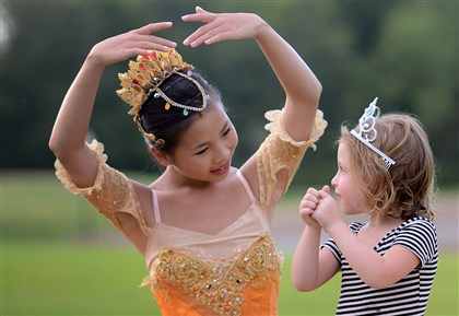 "20140817jrBalletFeature Chloe Olson, 13, helps Ellie Rizk, 4, of Morningside, strike a ballet pose before the start of the Pittsburgh Ballet Theatre's ""Ballet Under the Stars."""