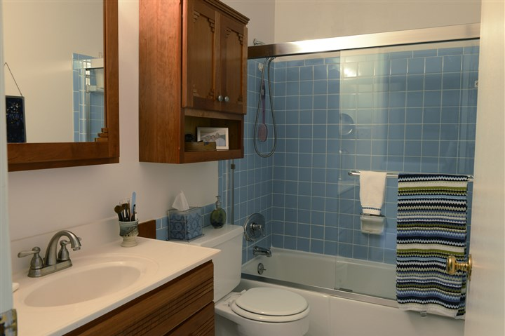 Buying Here: Scott The main bathroom features white walls and blue ceramic tile. The vanity, sink and wall storage are all in a warm oak.