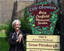 Mary Collins, office manager of the Allegheny YMCA on the North Side poses for a portrait in The Boxy Caufield Memorial Garden on the grounds of the YMCA.