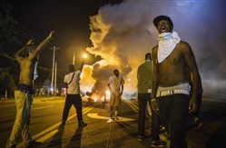Demonstrators stand in the middle of a street in Ferguson, Mo., as they react to tear gas fired by police during ongoing protests Tuesday night.