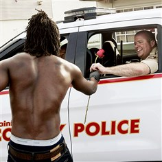 stLouis668-1 Resident John West, left, hands a rose to a police officer on Tuesday, showing his appreciation with help in cleanup efforts in Ferguson, Mo. Dangerous protests continued overnight as police fired tear gas and rubber bullets, shots were reportedly fired by people in the crowd and crowds failed to disperse.