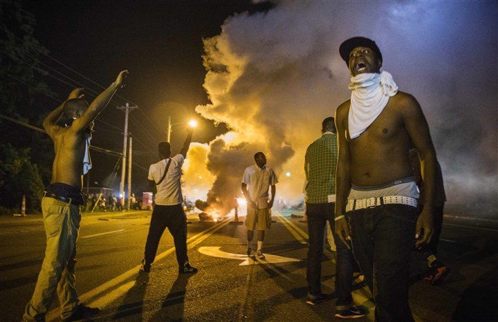 USA-MISSOURI/SHOOTING Demonstrators stand in the middle of a street in Ferguson, Mo., as they react to tear gas fired by police during ongoing protests Tuesday night.