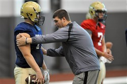Ryan Turnley, right, works on a stance with Gabe Roberts during a Pitt football practice Wednesday on the South Side. Turnley, a former center for the Panthers, is now a graduate assistant.