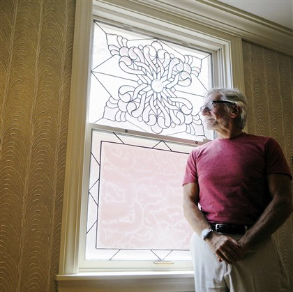 Lawyer-turned-artist Glenn Olcerst is self-taught in creating glass and stone pieces. Here, he poses in front of one of six stained glass windows that he created for his North Side home.