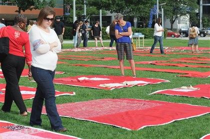National Sexual Violence Conference quilt Onlookers walk through rows of quilts containing messages from survivors of sexual assault Wednesday at Point State Park as part of the National Sexual Violence Conference happening this week in Downtown Pittsburgh.