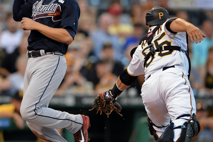 20140819mfbucssports09-1 Matt Freed/Post-Gazette August 19, 2014 Braves' Andrelton Simmons scores against Pirates' Russell Martin in the second inning at PNC Park Tuesday night.