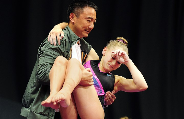 20140820jrGymSports5-3 Coach Liang Chow carries Rachel Gowey after she fractured her right ankle on her dismount from the balance beam Wednesday at Consol Energy Center.