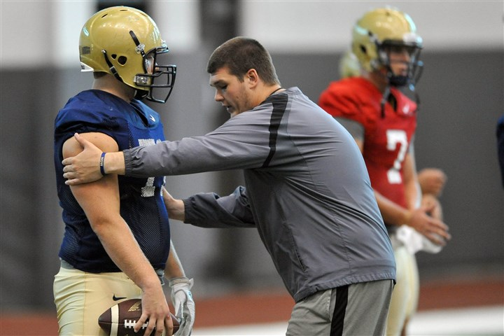 20140820MWHpittfootballSports02-1 Ryan Turnley, right, works on a stance with Gabe Roberts during a Pitt football practice Wednesday on the South Side. Turnley, a former center for the Panthers, is now a graduate assistant.