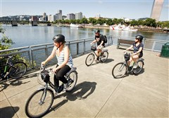 Riders enjoy the views of downtown Portland, Ore., across the Willamette River as they cruise the Eastbank Esplanade during a tour with the Cycle Portland bike tour company.