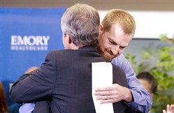 Ebola victim Kent Brantly, right, hugs a member of the medical staff that treated him. He was released from Emory University Hospital on Thursday.