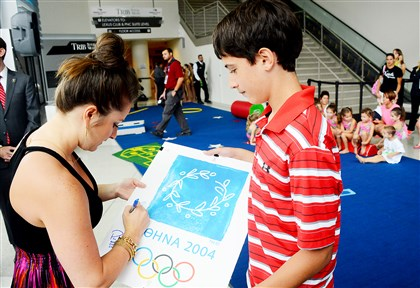 20140821lfGymLocal01 Carly Patterson, 2004 Olympic all-around champion, signs an autograph for Ben Popko, 12, of Canonsburg on Thursday during the P&G Gymnastics Championships Opening Celebration at the Consol Energy Center.