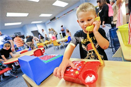 20140819JHWestPreK02-1 Four-year-old Ryan Dodd makes a call in one of the two newly remodeled Pre-K classrooms at J.W. Burkett Elementary School in Robinson. Ryan will attend the afternoon session when school opens.