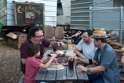 "FOODMOVIES183 ""Chef"" included a stop at Franklin Barbecue in Austin, Texas. From left, Emjay Anthony, Jon Favreau, Aaron Franklin and John Leguizamo."