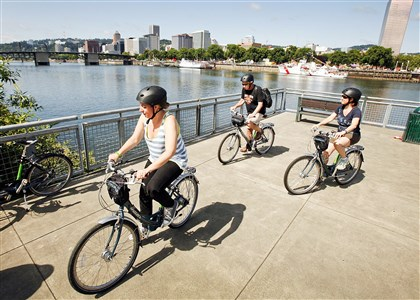 PORTLANDBIKE9 Riders enjoy the views of downtown Portland, Ore., across the Willamette River as they cruise the Eastbank Esplanade during a tour with the Cycle Portland bike tour company.
