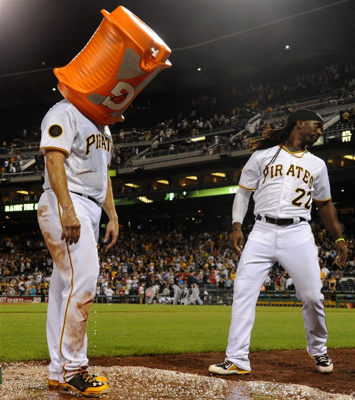 20140820mfbucssports12-4 Gaby Sanchez stands with a Gatorade bucket on his head after Andrew McCutchen and Josh Harrison dumped ice water on him after he hit a walk-off sacrifice fly against the Braves in the ninth inning at PNC Park Wednesday night, August 20, 2014.