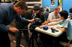 "The Same Difference Film team, including Kyle Wentzel and Joshua Sweeny, filming Graeme Taylor playing a game of ""Magic: The Gathering"" with friends at GameStop in Ann Arbor, MI."