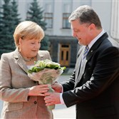 Ukraine President Petro Poroshenko, right, welcomes German Chancellor Angela Merkel with a bouquet of flowers before their meeting Saturday in Kiev, Ukraine.