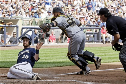 Pirates Brewers Baseball Milwaukee Brewers' Jonathan Lucroy slides safely past Pirates catcher Russell Martin during the second inning of this afternoon's game in Milwaukee. Lucroy scored from second on a hit by Aramis Ramirez. The Pirates ended up winning, 4-3.