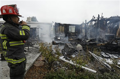 California Earthquake Napa Fire Capt. Steve Becker inspects mobile homes destroyed early today in Napa, Calif., as a result of a gas fire that ignited during the earthquake.
