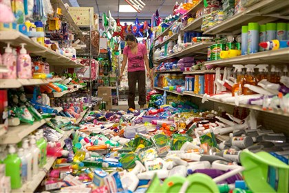 APTOPIX California Earthquake Nina Quidit cleans up the Dollar Plus and Party Supplies Store in American Canyon, Calif. after today's earthquake.