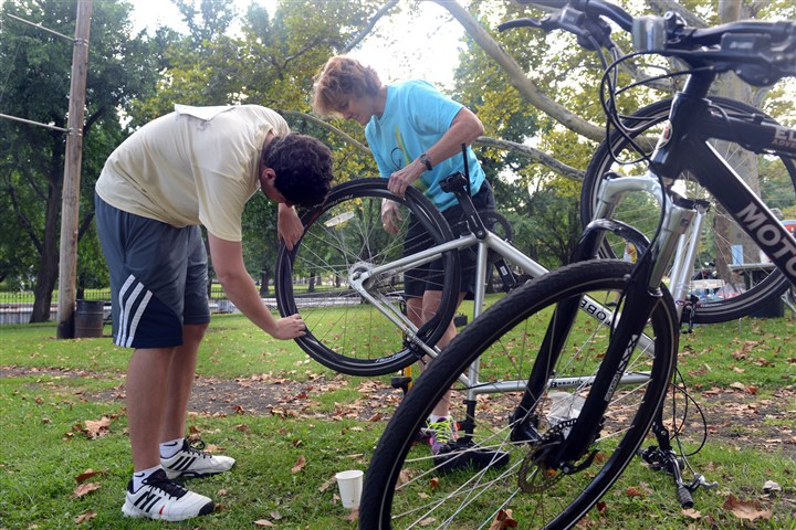 Pedal Pittsburgh West Park rest stop Patrick Driscoll of Shadyside gets some help fixing his tire from Beth Hazlett at a rest stop in West Park for the Pedal Pittsburgh event. Ms. Hazlett is on the board of Bike Pittsburgh and was working as a volunteer at the stop.