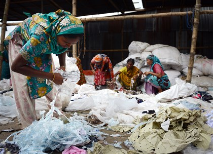Women pick through scraps of fabric and jute in Kashimpur, Bangladesh. They wade through wet and often soiled scraps, making less money than garment workers, and work is never guaranteed.