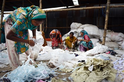 Women pick through scraps of fabric and jute in Kashimpur, Bangladesh. They wade through wet and often soiled scraps, making less money than garment workers.