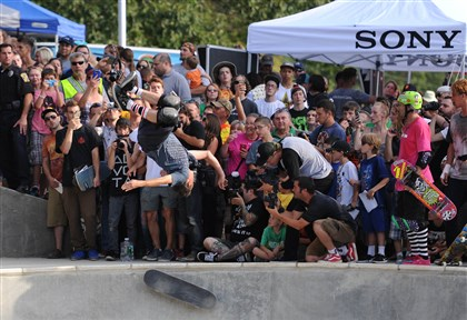 professional skateboarder Tony Hawk  To end his demonstration, professional skateboarder Tony Hawk flips off his skateboard at Pitcher Park Memorial Skatepark in Carnegie on Monday.