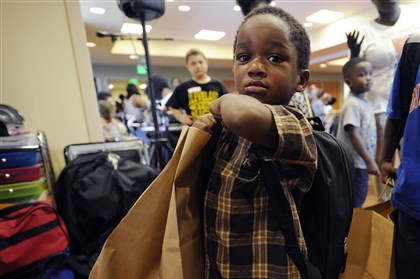 20140822CMBackpackEast001 Joshua Miles, 3, of Wilkinsburg labors to collect his backpack, school supplies and non-perishable food items given to him by the Wilkinsburg School District at the backpack giveaway event held at the LifeCare Hospitals of Pittsburgh in Wilkinsburg.