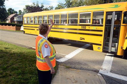 University Park Elementary School crossing guard Carolyn Boone waves to children Aug. 25 as their bus turns into the driveway to University Park Elementary School in Monroeville on the first day of school.