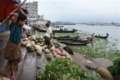 09012014jrBangladeshLocal10-1 Men sell vegetables along the Buriganga River in Old Dhaka, Bangladesh.