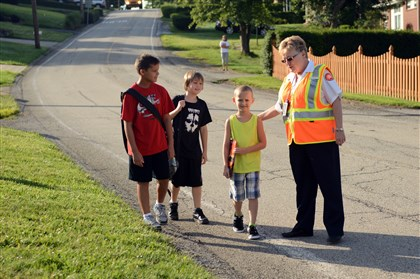 20140825RARzonescrossing1-1 Carolyn Boone chats with children heading to their first day of school Aug. 25 in Monroeville.