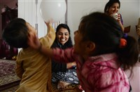 "Bhutanese refugees Bhim Maya Poudyel, center, blows up balloons for Apson Thapa, 3, left, and Perika Poudel, 4, before a family birthday party at her apartment in Carrick. Bhim said birthdays are not a big deal and go without celebration in Nepal. ""The kids learn about birthday parties in school,"" she said."