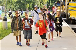 Children arrive on buses for classes at Penn Hills Elementary Center.