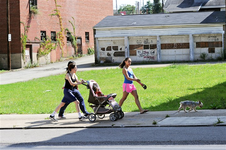 20140825JHLocalClairton02-1 Residents walk past a lot along St. Clair Avenue that was cleaned up with Act 47 money when vacant buildings were razed.