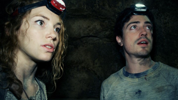 "AsAboveSoBelow2-1 Perdita Weeks and Ben Feldman traverse miles of twisting catacombs beneath the streets of Paris in ""As Above/So Below."""