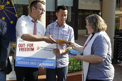 Gay Marriage Indiana Rev. Melody Merida, of the Life Journey Church, hands out signed heart-shaped cards to Greg Hasty, left, and CJ Vallero following at a rally in Indianapolis, Monday, Aug. 25, 2014 for gay couples that are part of a court hearing on the challenge to Indiana's same-sex marriage ban. Nearly 100 supporters gathered at the City Market in downtown Indianapolis to see off some of the plaintiffs as they left to attend legal arguments before a federal appeals court on Tuesday. (AP Photo/Michael Conroy)