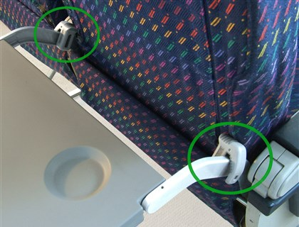 kneedefender2 08272014 The knee defender is attached to the airline seat's tray table.