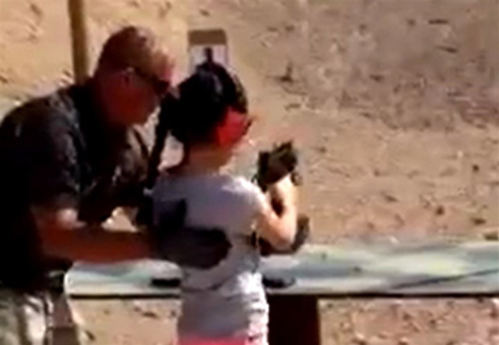 SHOOTINGARIZONA-12 Shooting instructor Charles Vacca stands next to a 9-year-old girl at the Last Stop shooting range in White Hills, Ariz., on Monday. The girl accidentally shot and killed her shooting instructor with an Uzi when the weapon's strong recoil caused her to lose control of her aim, police said.