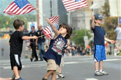 BDominic Truckley, 4, of Penn Hills leads a flag-waving frenzy along the Boulevard of the Allies by Robert Kennedy, left, 4, of Mt. Lebanon and Koen Melder, right, 5, of Friendship during the 2012 Labor Day Parade.