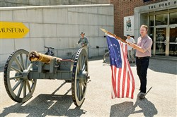 Mike Burke, an exhibit specialist at Fort Pitt Museum, gets the day going  by bringing out the original 13-star flag to place on the cannon in front of the museum entrance on Aug. 28, 2014.