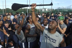 Penn State's Brandon Bell, foreground, and other members of the NCAA college football team cheer after they received lessons in hurling and Gaelic football at University College in Dublin, Ireland on Thursday.