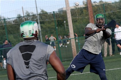 psu0829d-3 Penn State's C.J. Olaniyan, right, and other members of the NCAA college football team receive lessons in hurling and Gaelic football at University College in Dublin, Ireland, Thursday.