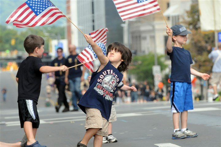 Staff Photographer BDominic Truckley, 4, of Penn Hills leads a flag-waving frenzy along the Boulevard of the Allies by Robert Kennedy, left, 4, of Mt. Lebanon and Koen Melder, right, 5, of Friendship during the 2012 Labor Day Parade.