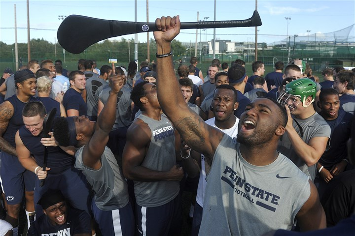 psu0829a Penn State's Brandon Bell, foreground, and other members of the NCAA college football team cheer after they received lessons in hurling and Gaelic football at University College in Dublin, Ireland on Thursday.