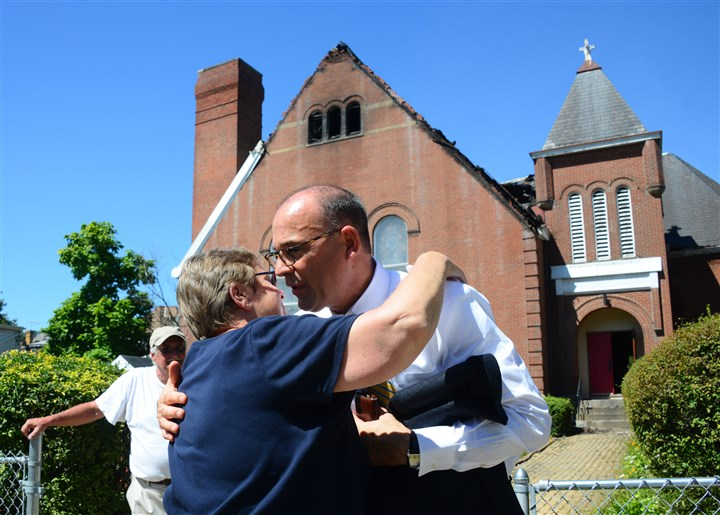 20140829lfFireLocal01 Pittsburgh City Council president Bruce Kraus comforts Rev. Sue Hutchins of Hilltop United Methodist Church in Allentown after a three-alarm fire ripped through the roof of the church the day before.